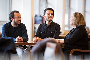 Chilean medical students (from left) José Pablo Muñoz Salas and Juan Ignacio Guerra chat with Jill Raufman in the Einstein Café